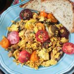 tofu scramble with mushrooms and tomatoes on a blue plate