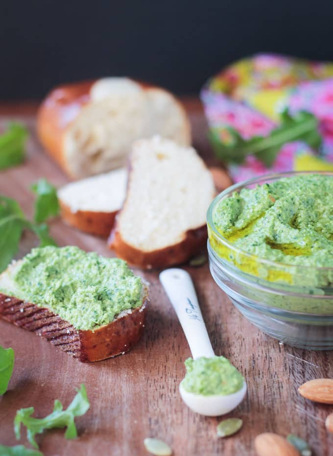 Pesto spread on a slice of fresh bread next to a small bowl of pesto with fresh bread in the background.