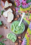 Spoon in a small bowl of pesto, slice or bread spread with pesto in front, two slices of fresh bread behind.
