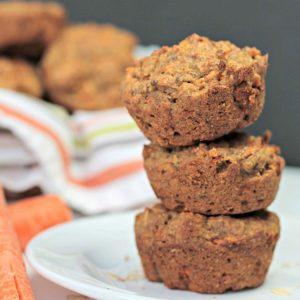 Stack of 3 vegan carrot oat muffins on a white plate.