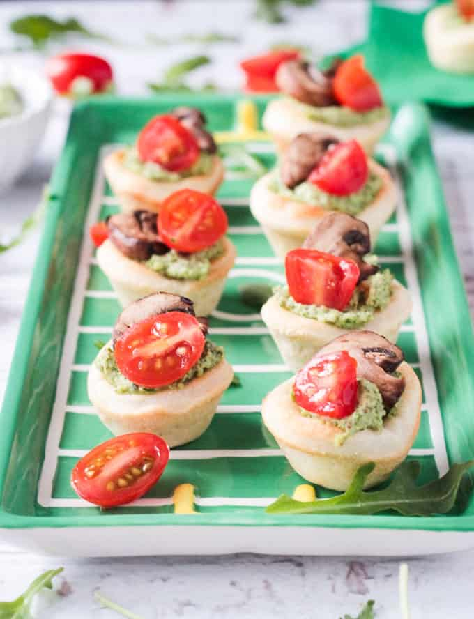 Tray of vegan pizza bites topped with pesto, cherry tomatoes, and mushrooms.