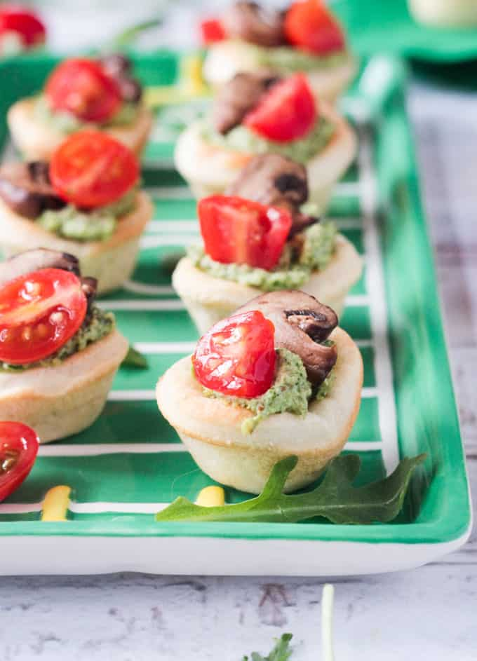 Pizza dough formed into little bite size cups filled with pesto, tomatoes, and mushrooms.