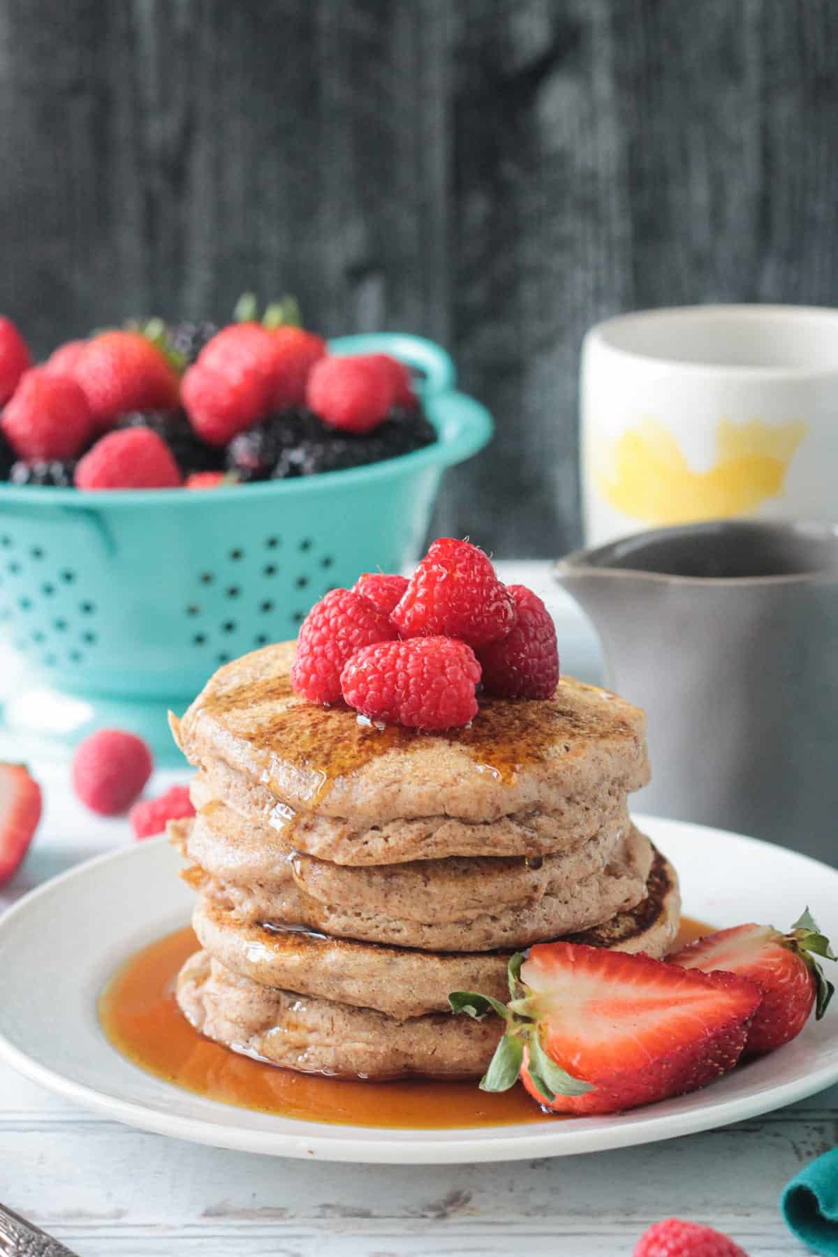 stack of pancakes topped with fresh berries and syrup