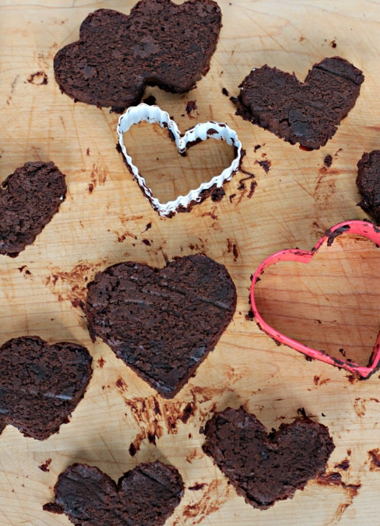 Fudgy Mocha Black Bean Brownies cut into various heart shapes on a wooden board. One white and one red heart cookie cutter on the board as well.