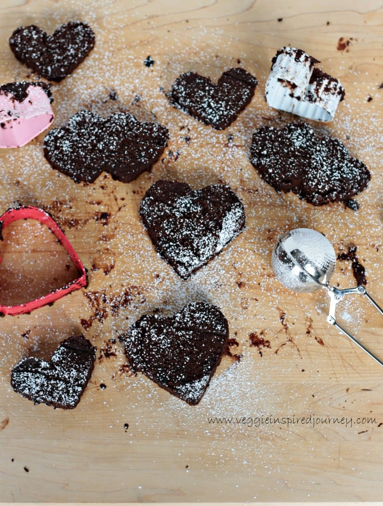 Overhead view of a batch of Fudgy Mocha Black Bean Brownie Hearts next to heart shaped cookie cutters and a small mesh tea ball infuser used to sprinkle powdered sugar.