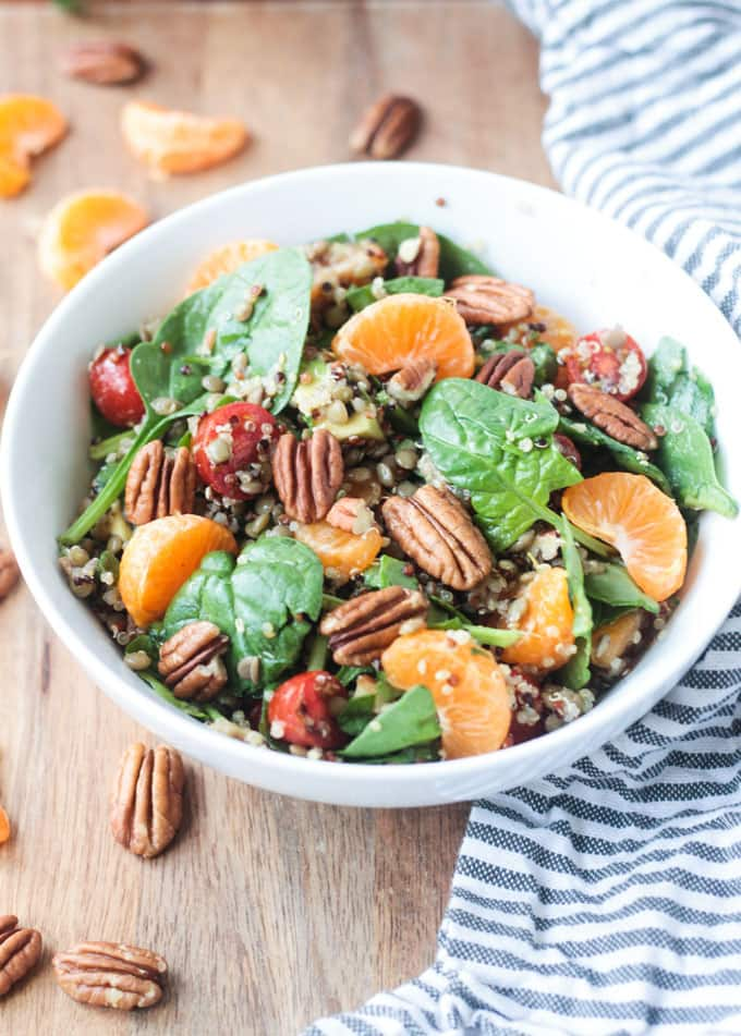 Salad of spinach, orange slices, tomatoes, quinoa, lentils, & pecans in a white bowl next to a gray and white striped dish towel.