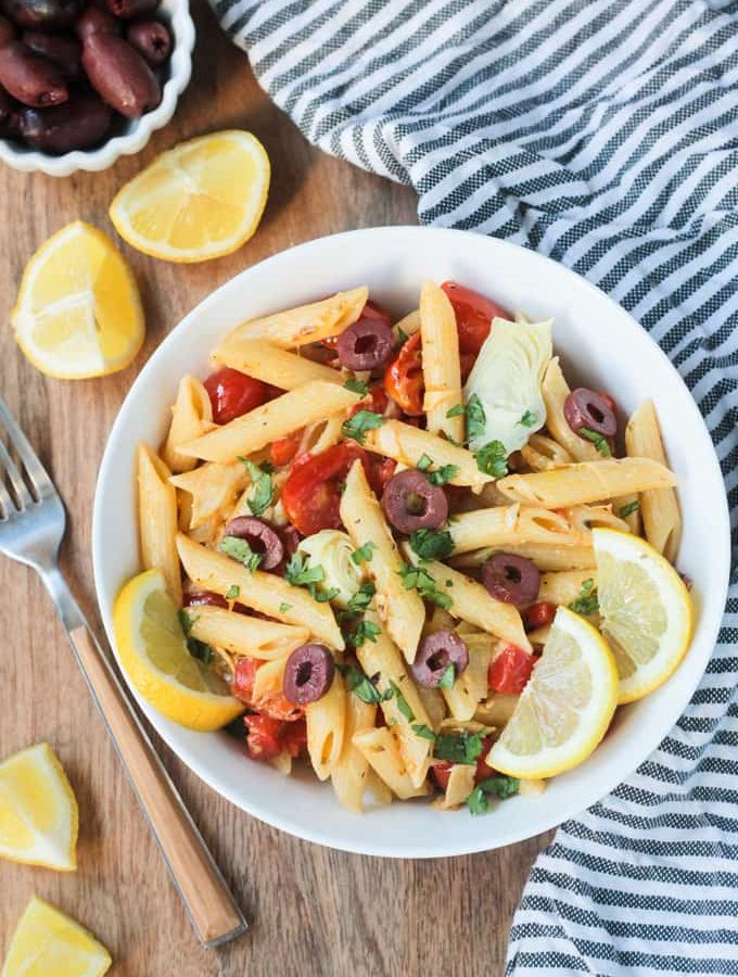 Overhead shot of a bowl of penne pasta w/ vegetables & garnished with lemon slices. A gray & white striped dish towel lies next to the bowl on the right. A fork, lemon wedges, and a small bowl of olives is on the left side of the bowl.