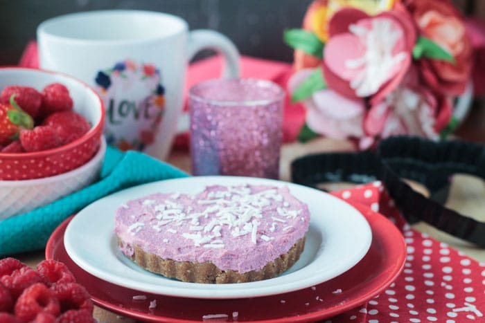 Pink hued dairy free cheesecake tart on a white and red plate. Red bowl of fresh berries, coffee mug, pink candle, and flowers in the background.