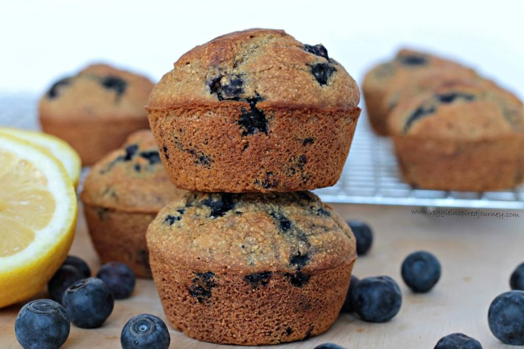 Two blueberry cornmeal muffins stacked on top of each other. Fresh blueberries scattered around.