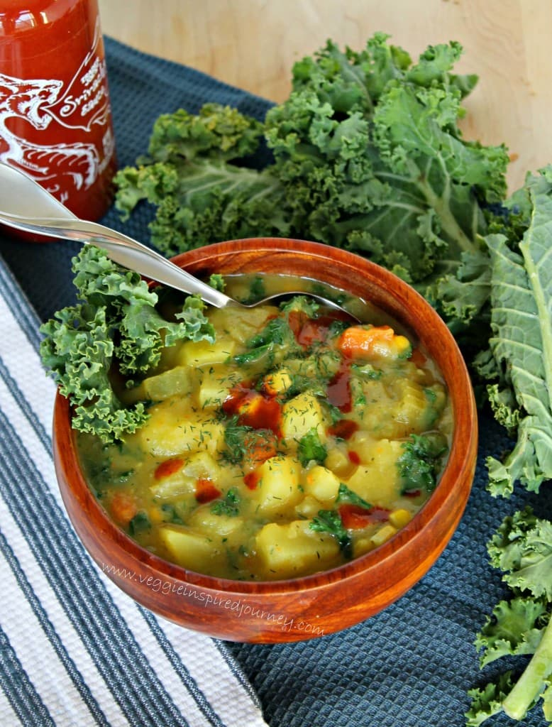 Silver spoon in a wooden bowl of potato soup topped with hot sauce. Curly kale leaves next to the bowl and a bottle of hot sauce in the background.