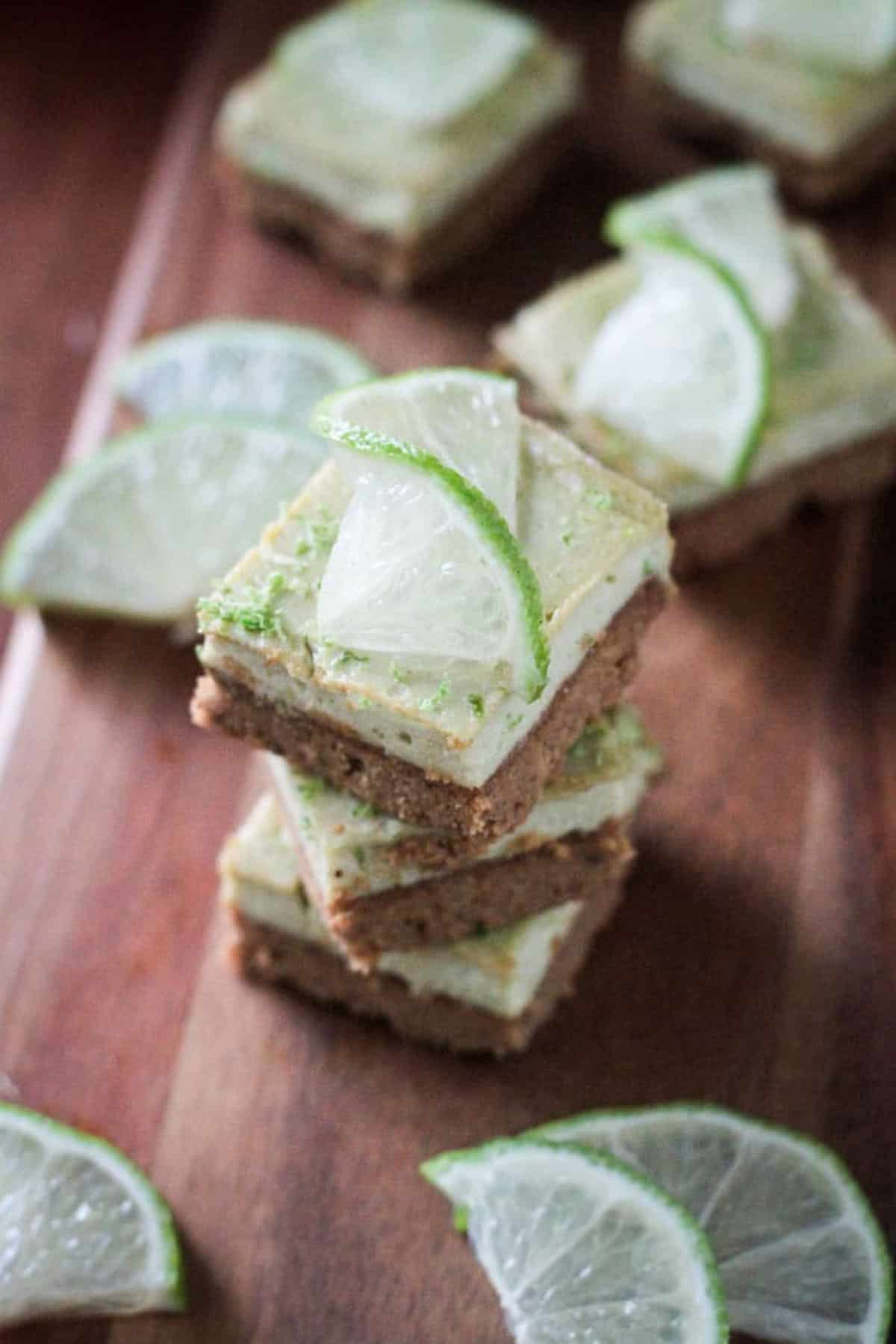 Stack of 3 vegan lime bars topped with a twisted lime wedge.