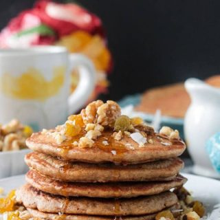 Front view of a stack of carrot cake pancakes drizzled with maple syrup.