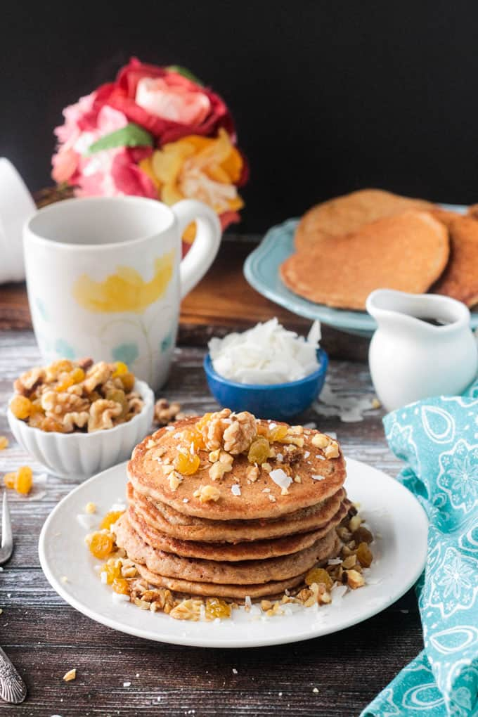 Stack of carrot cake pancakes with small bowls of walnuts and coconut flakes, a cup of coffee, and a blue plate of more pancakes.