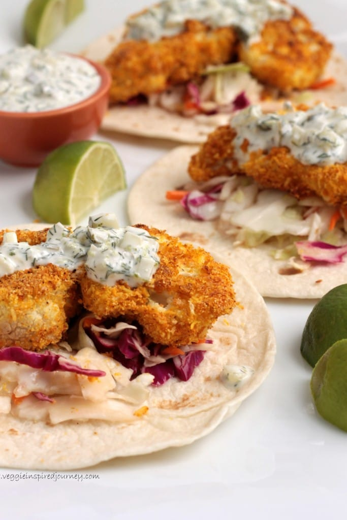 Three crispy cauliflower tacos on flour tortillas topped with dill tartar sauce.