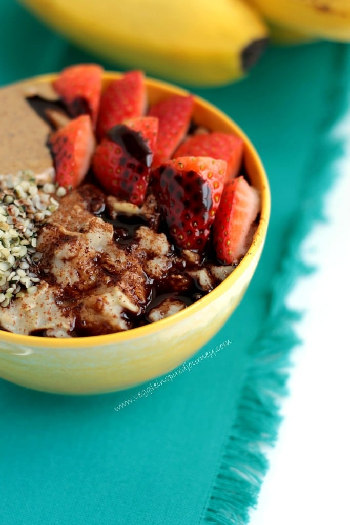 Creamy oatmeal, in a yellow bowl, topped with strawberries and a drizzle of cocoa syrup.