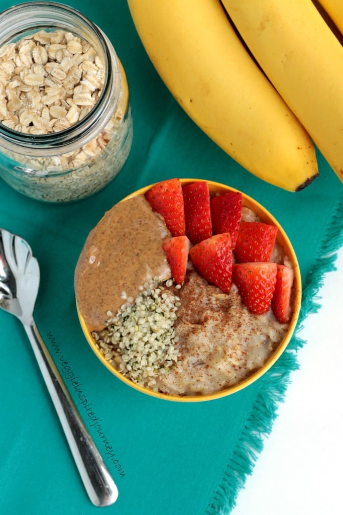 Bowl of oatmeal topped with strawberries, nut butter, hemp seeds, and cinnamon. Jar of oats and bunch of bananas in the background.