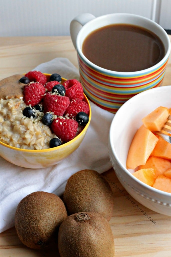 Bowl of berry topped oatmeal, multi-color striped cup of coffee, bowl of cantaloup chunks, and 3 kiwifruit.