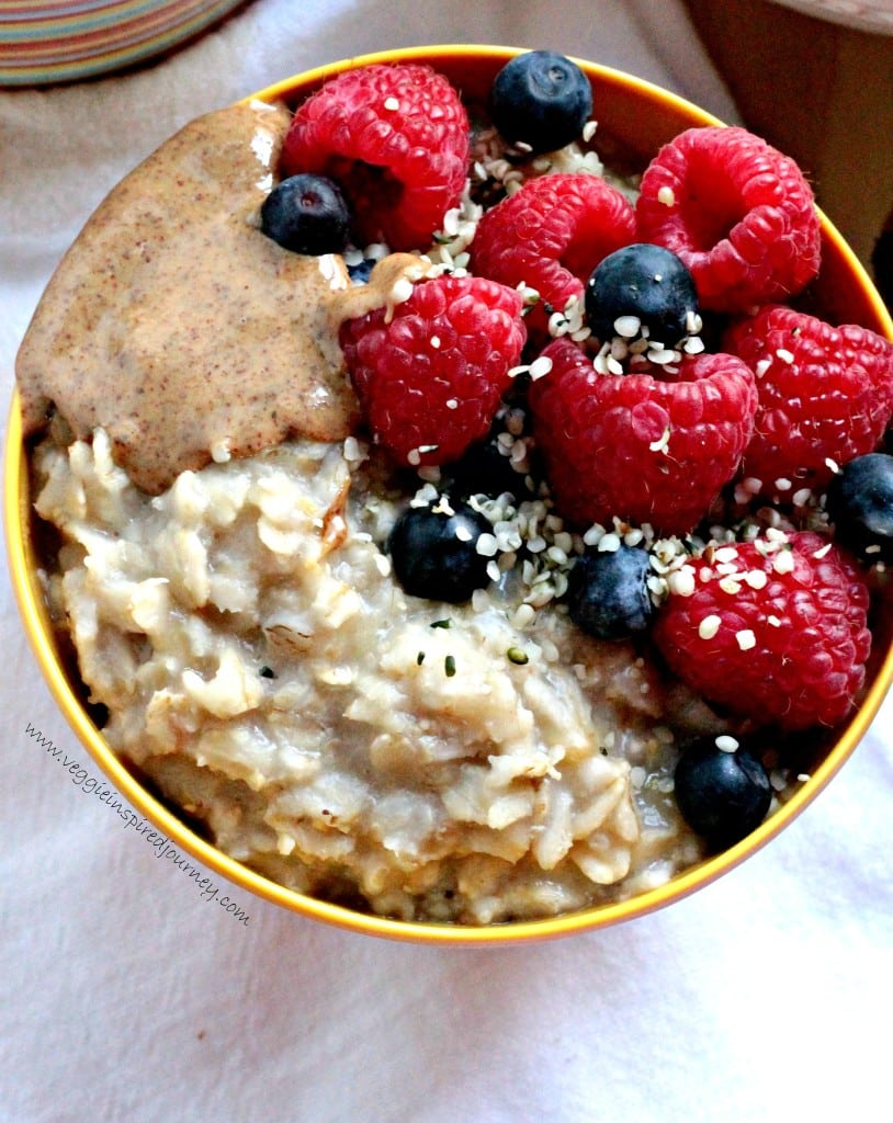 Yellow bowl of creamy oatmeal topped with almond butter, raspberries, blueberries, and hemp seeds.