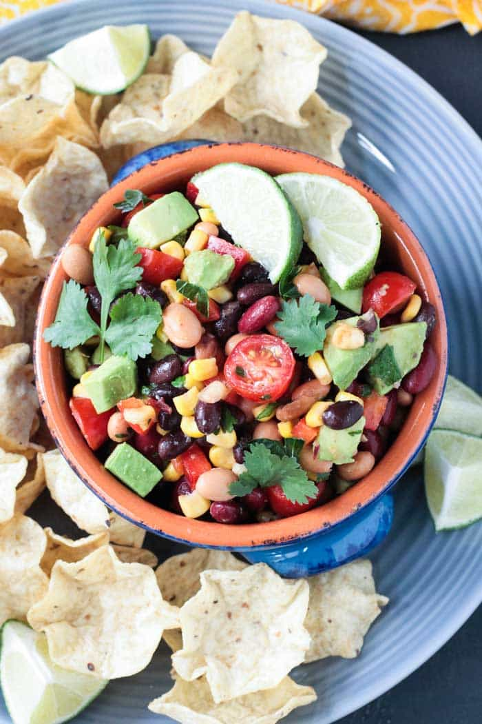 Smoky Cilantro Lime Mexican Bean Dip in a bowl with tortilla chips on a gray plate.