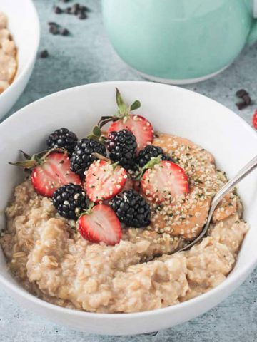Spoon in a bowl of creamy oats with fresh berries and hemp seeds.