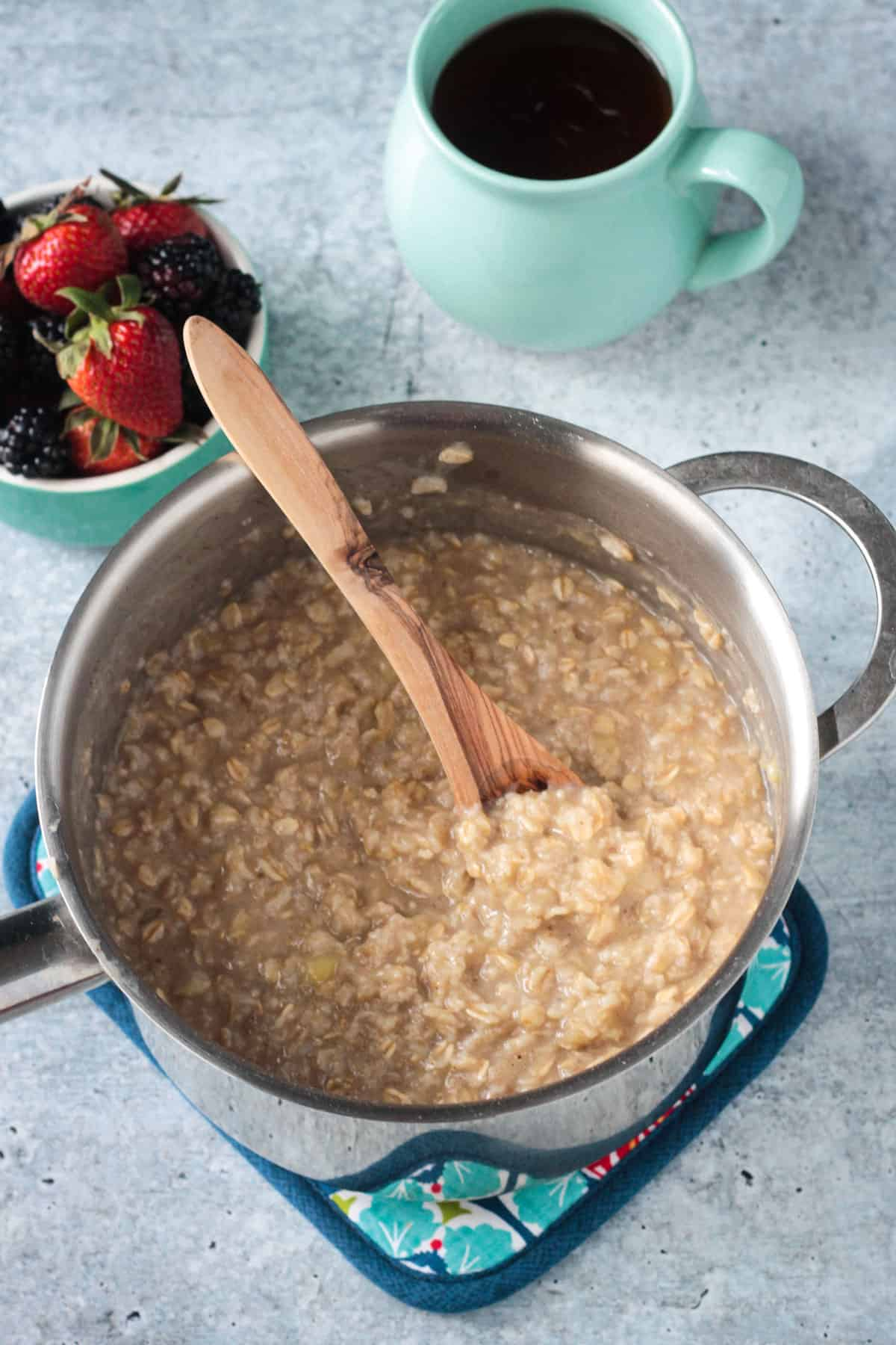 A wooden spoon stirring a pot of creamy oatmeal.