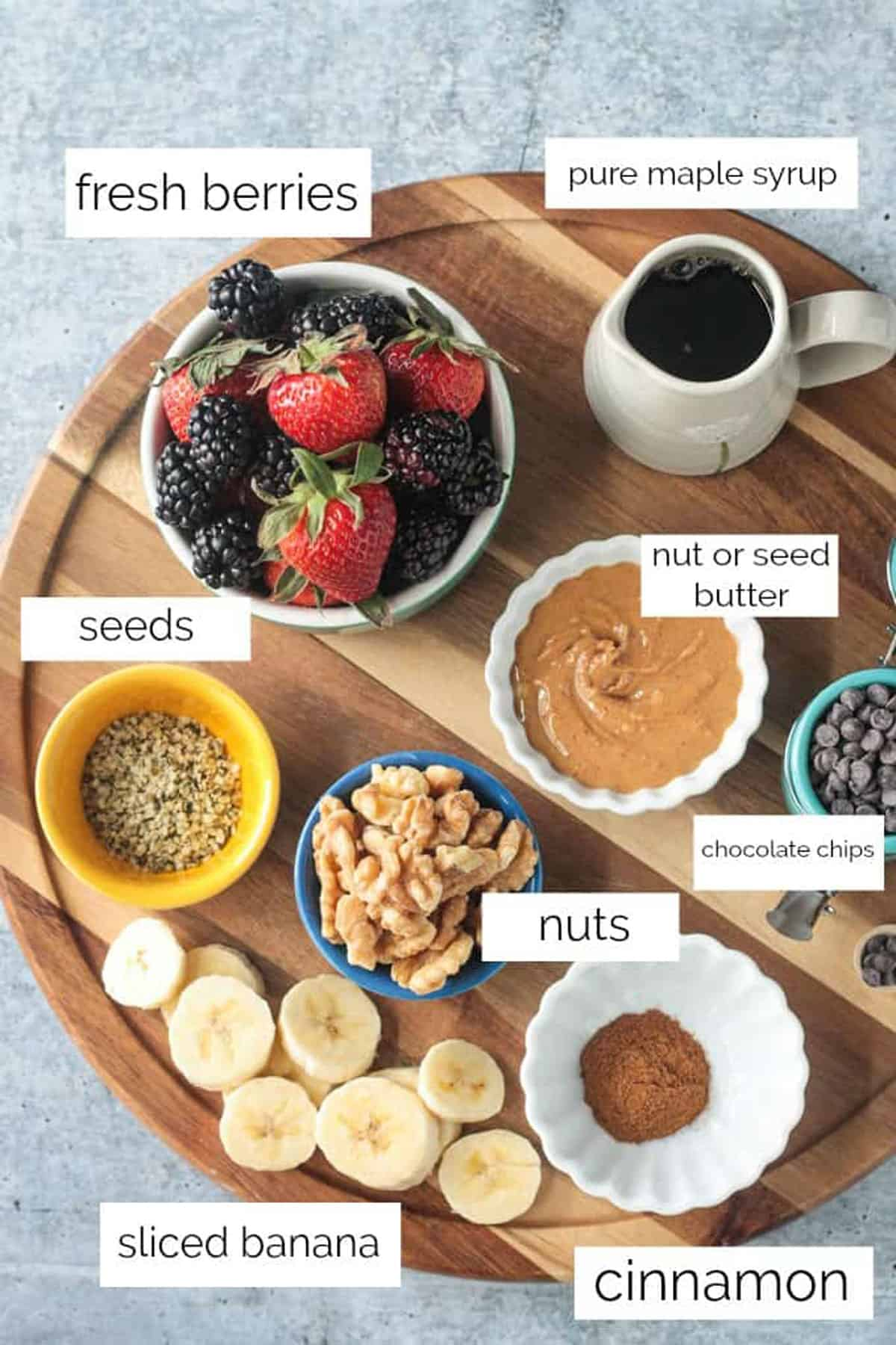 Topping ingredients arrayed in individual bowls on a wooden serving tray.