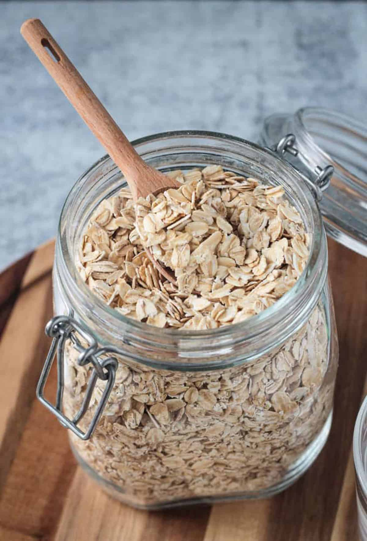 Raw rolled oats in an open glass jar with a wooden spoon.