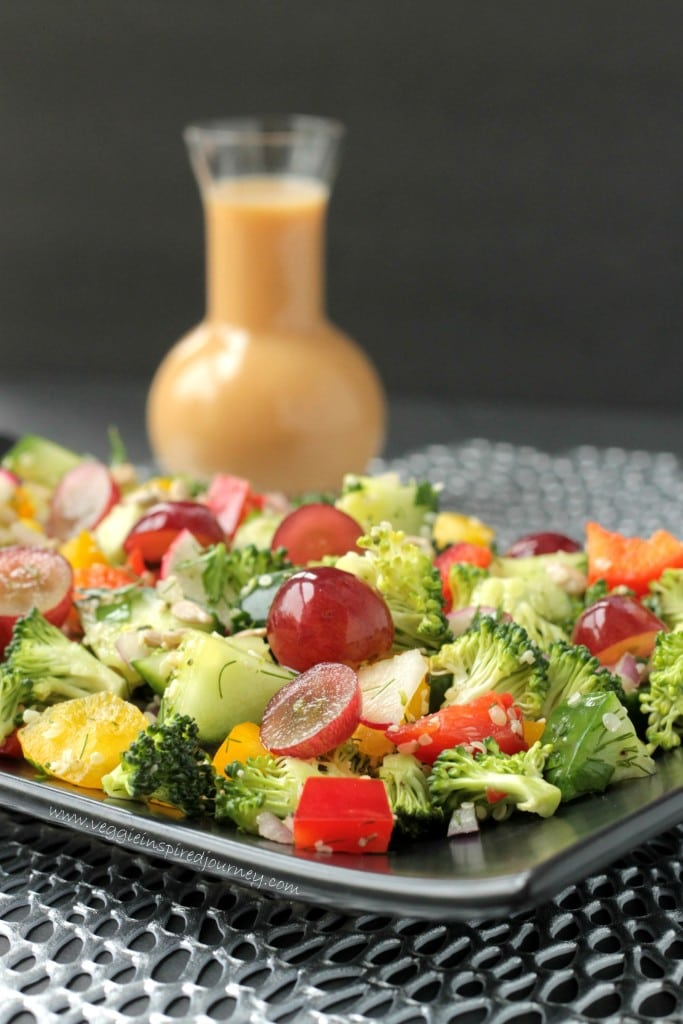 Broccoli, red peppers, red grapes, cucumbers, and hemp seeds mingle on a black plate. Small jar of salad dressing in the background.