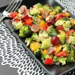 vegetable salad on a black plate with a fork