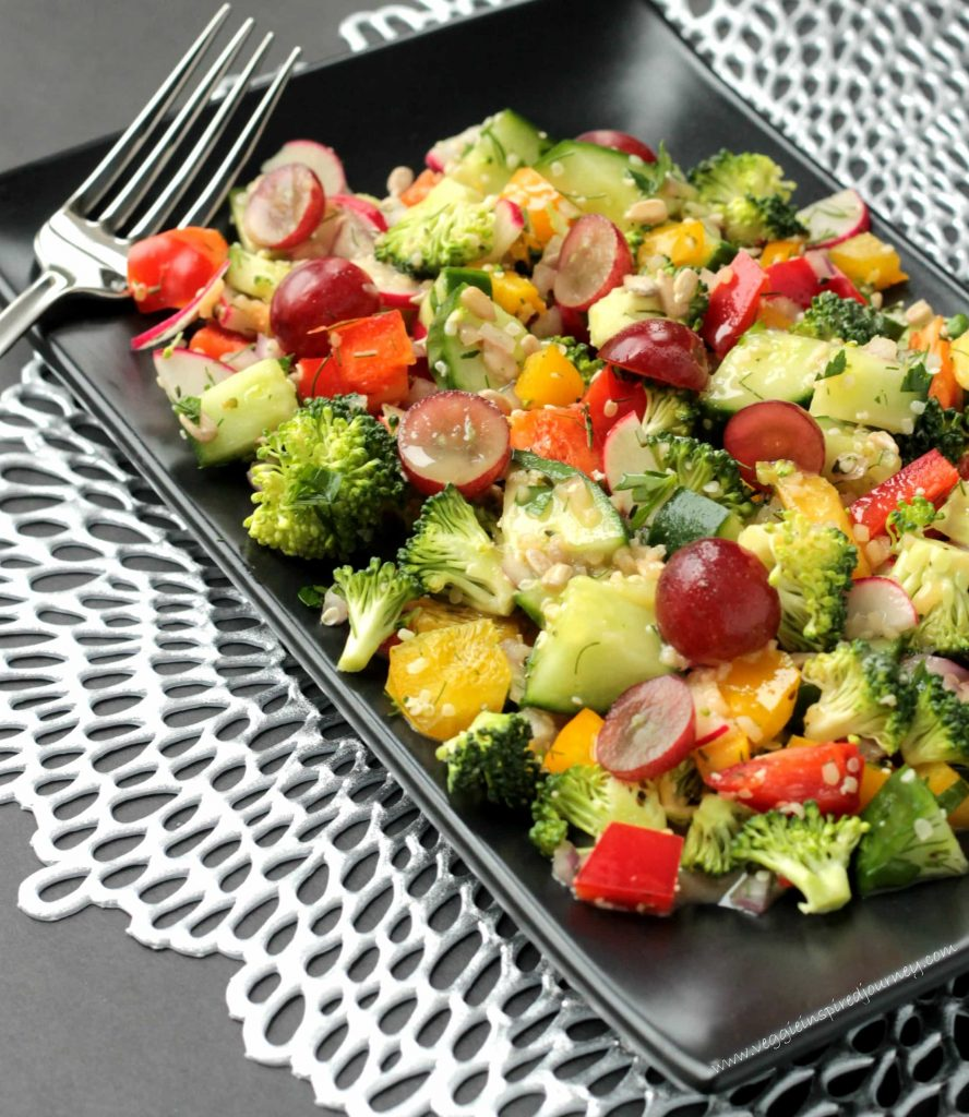 Salad of raw chopped vegetables on a black rectangular plate. A silver fork rests on the edge.