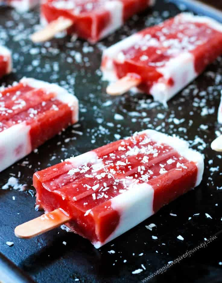 Strawberry Rhubarb Coconut Milk Popsicles laid out flat on a black tray and sprinkled with shredded coconut.