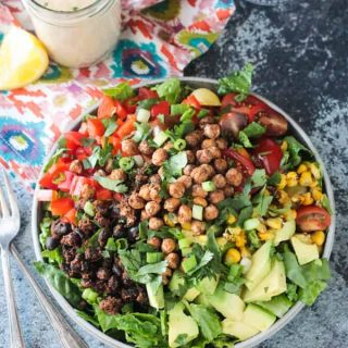 Big plate of salad with avocado, black beans, red peppers,tomatoes, corn, and crunchy roasted chickpeas.