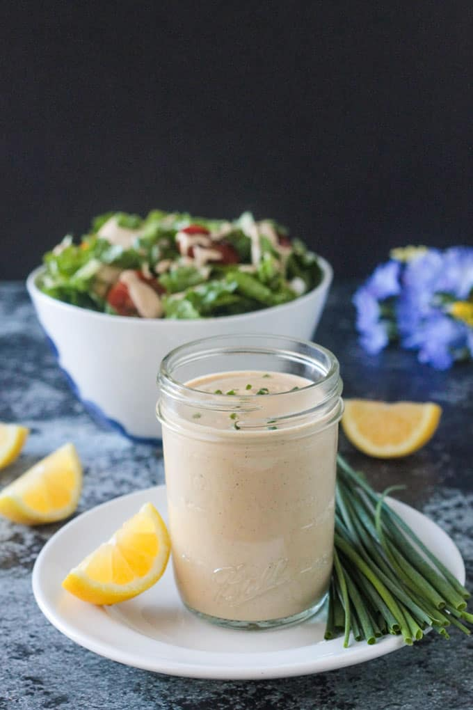Jar of vegan ranch dressing in front of a bowl of salad.