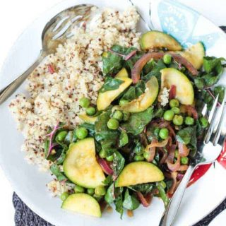 mixed spring veggies next to quinoa on a plate with utensils