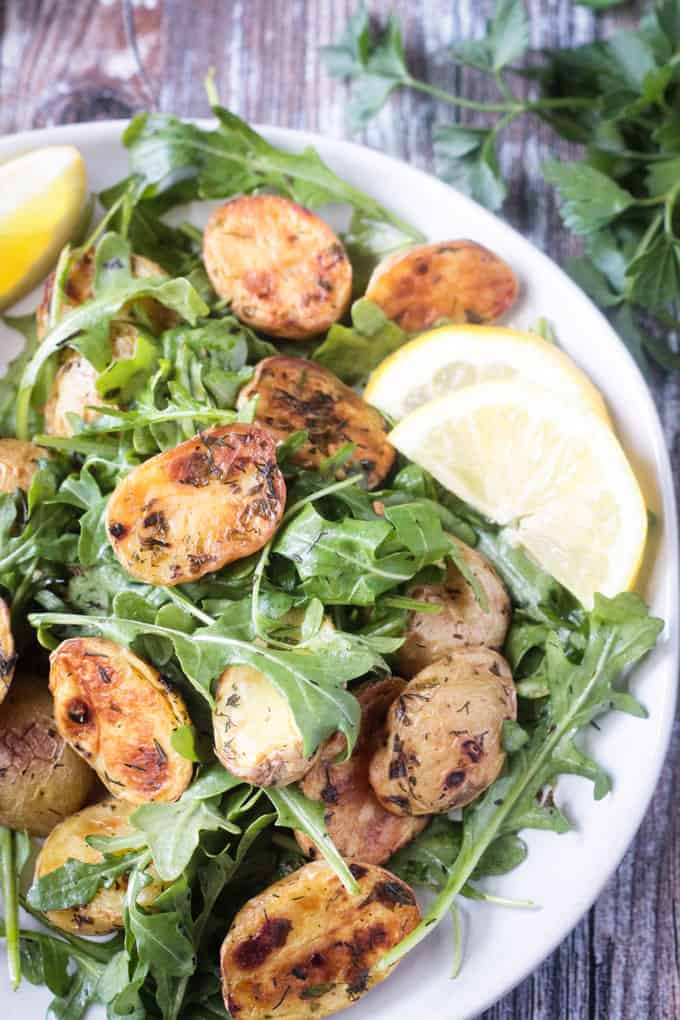 Close up overhead view of herb roasted potatoes on a bed of arugula. Two lemon slices on the side.