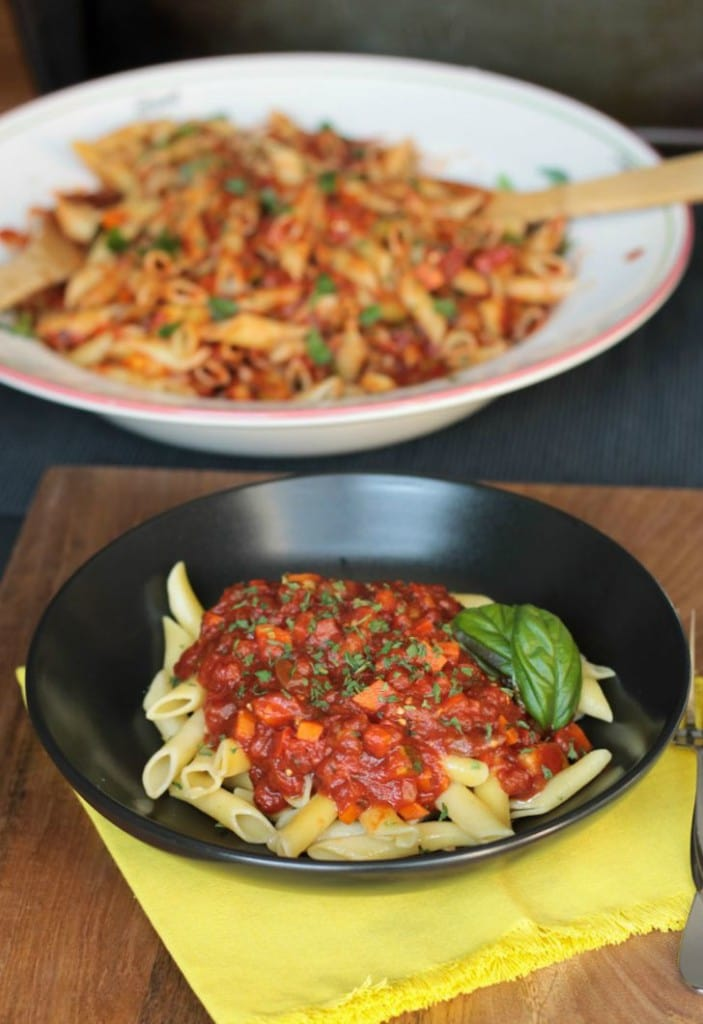 Chunky Veggie Marinara sauce over penne in a black bowl with fresh basil leaves. Behind is a big pasta bowl of pasta mixed with the sauce.
