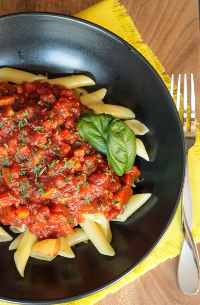 Overhead view of a bowl of pasta topped with Chunky Veggie Marinara Sauce. A fork lies on the table next to the bowl.