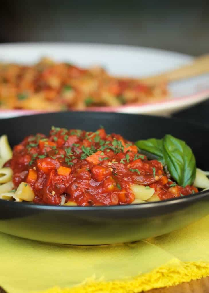 Chunky Veggie Marinara Sauce Over Penne Pasta In A Black Bowl