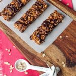 three granola bars drizzled in chocolate on a piece of parchment paper