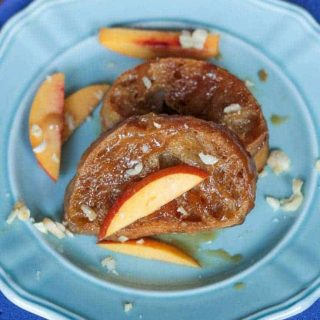 two slices of french toast on a blue plate with sliced peaches