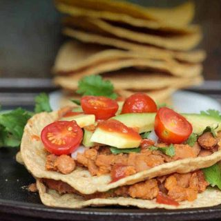 two tostada shells layered with refried beans, tomatoes, and avocado