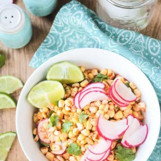 Corn Radish Salad in a white bowl garnished with cilantro leaves and lime wedges. Extra lime slices on the side with blue salt and pepper shakers in the background.
