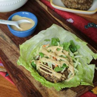 veggie burger in a lettuce leaf with sauce drizzled over the top