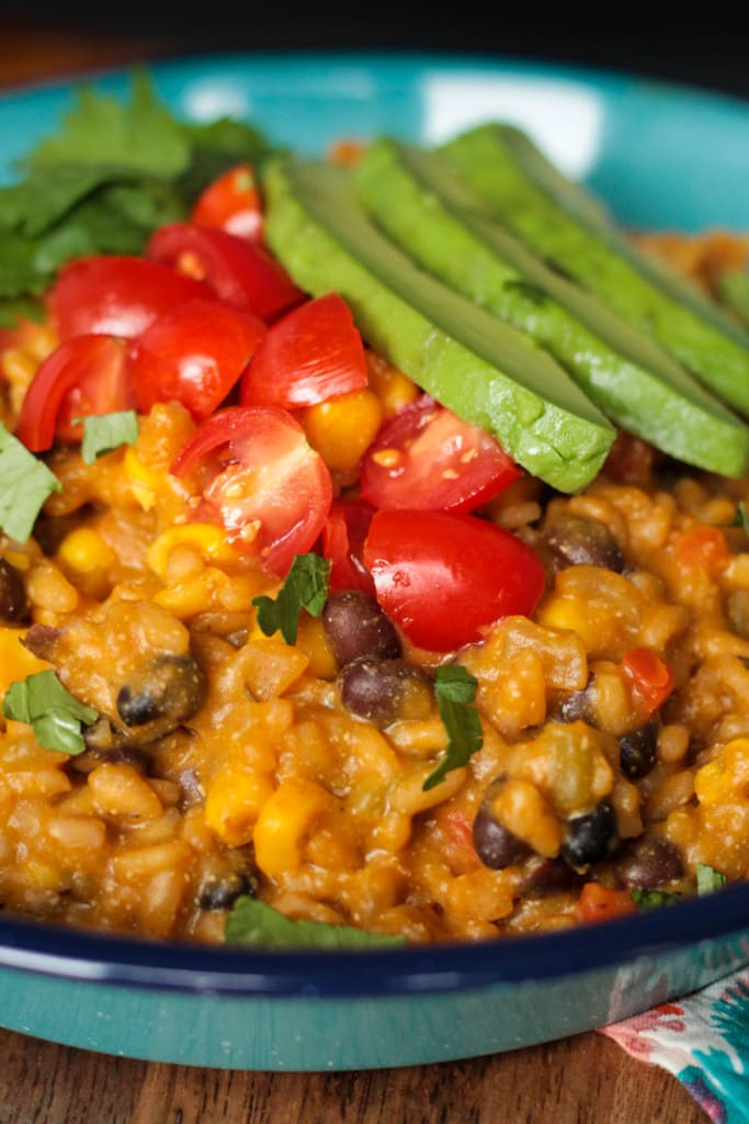 Close up of Southwest Pumpkin Vegan Risotto topped with halved cherry tomatoes and slices of avocado.