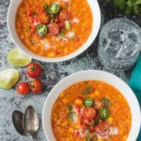 Two bowls of summer corn chowder topped with halved cherry tomatoes, jalapeno slices, and green onions.