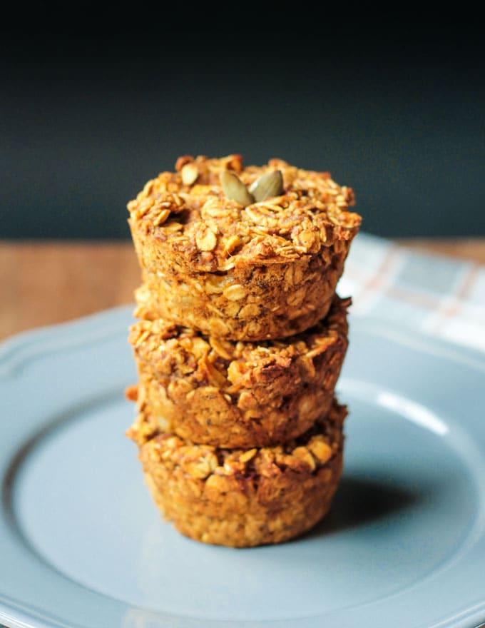 Stack of three Apple Pumpkin Pie Baked Oatmeal muffins on a blue plate.