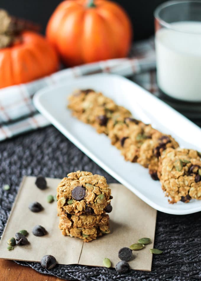 Small stack Pumpkin Oatmeal Chocolate Chip Cookies in front of more cookies lined up on a white rectangular platter. Glass of milk in the background.