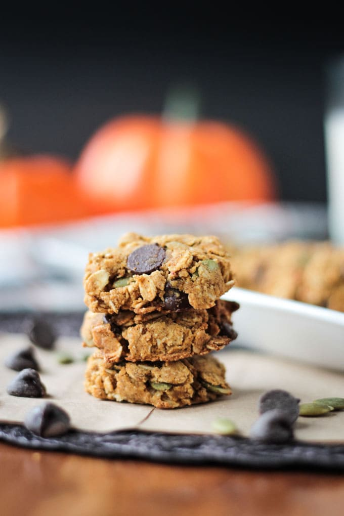Stack of Crunchy Gluten Free Pumpkin Oatmeal Chocolate Chip Cookies. Decorative orange pumpkins in the background.
