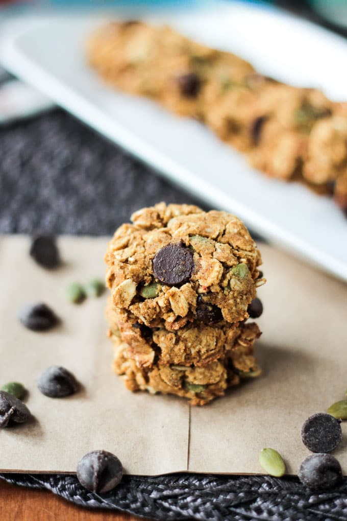 Stack of three Pumpkin Oatmeal Chocolate Chip Cookies. A white dish with a row of cookies blurred out in the background.