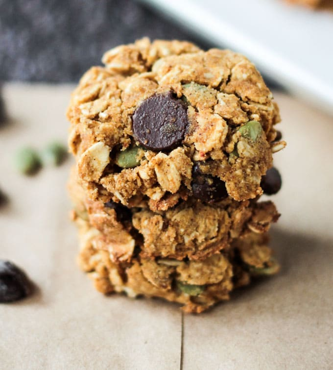 Close up view of a stack of three Pumpkin Oatmeal Chocolate Chip Cookies with pumpkin seeds on a piece of brown parchment paper.